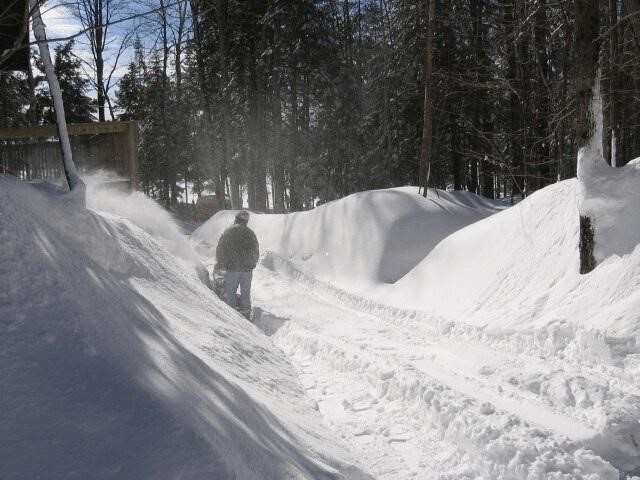 Large snowbanks on either side of a driveway as a cottager plows the snow