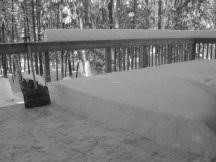 Deck partly shoveled showing thick layer of snow to still be shoveled off.
