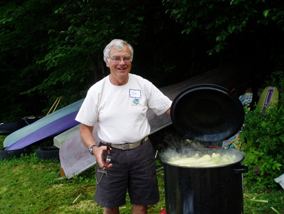 Man standing over a big pot of corn outside