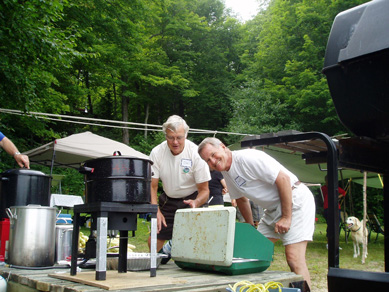 Two men standing over a BBQ at the annual corn roast