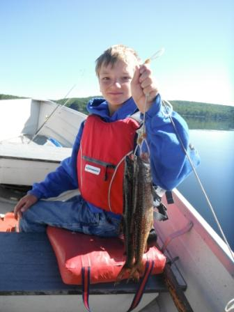 Leandro in a boat holding up two lake trout