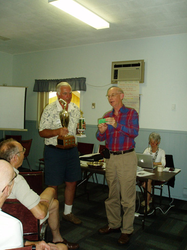 Harry Winder receiving the fishing trophy at the AGM (on behalf of his grandson) and Joe Matys presenting a special lure