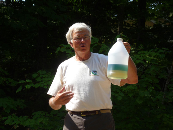 Jim Richert holding up a transparent can of separated gasoline