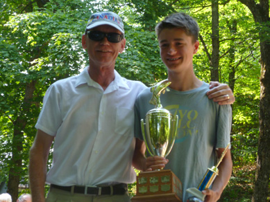 Dillon holding the youth fishing trophy with a man's arm around him