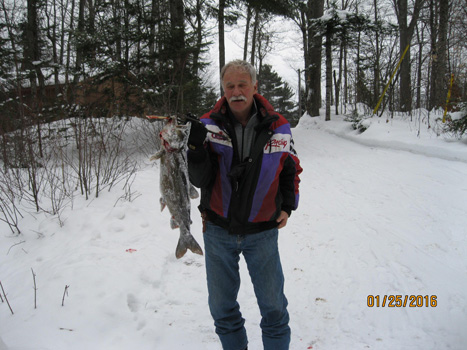 Ed holding up a fish in front of snow covered trees
