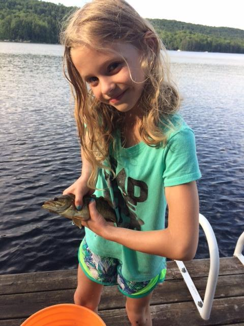 Sophia standing on the dock with a big smile on her face and holding a fish