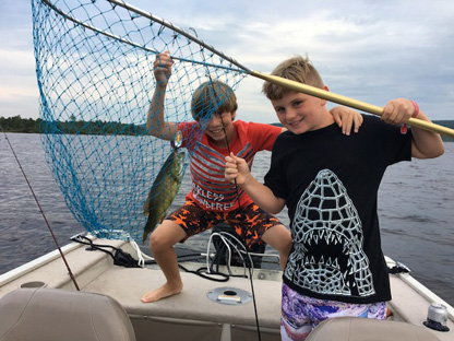 Julian and friend holding up a net with a fish inside
