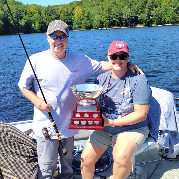 Mark and Jody Ristow in their fishing boat with the Percy Lake Bass Fishing trophy.