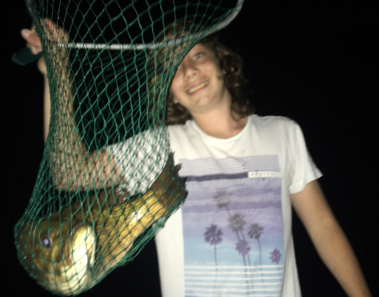 Julian Tilman holds a net up with a bass fish in it.