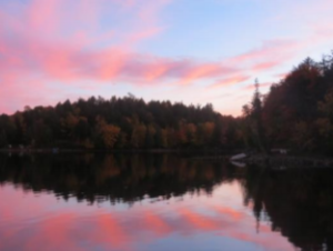 Percy Lake with a sunset reflecting on calm water.