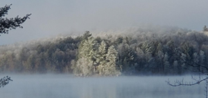 A misty shot of Percy Lake with snow covered trees.